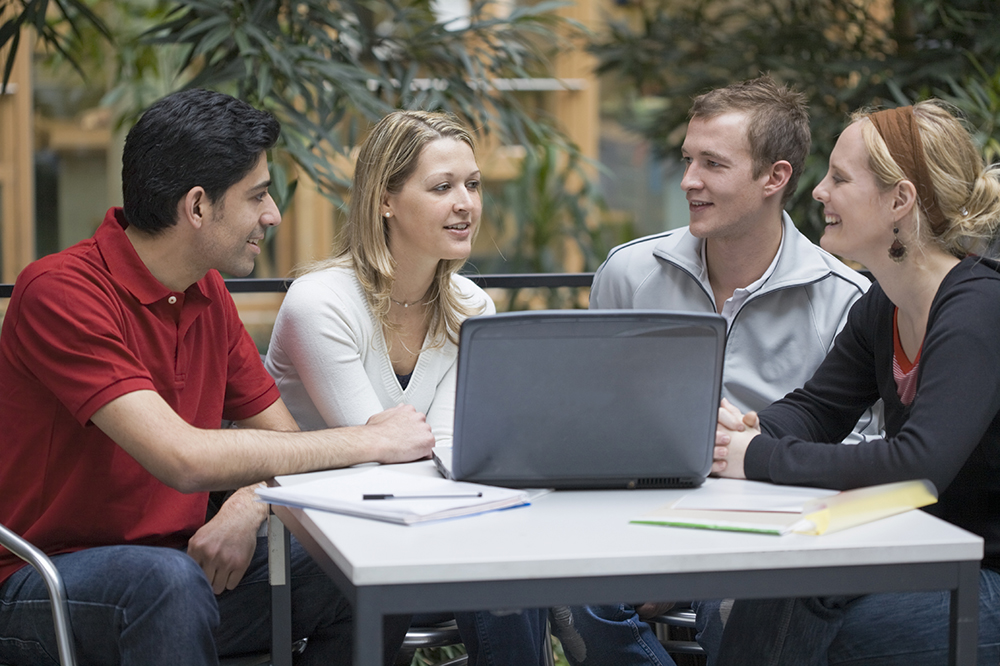 Group of young students sat around a laptop